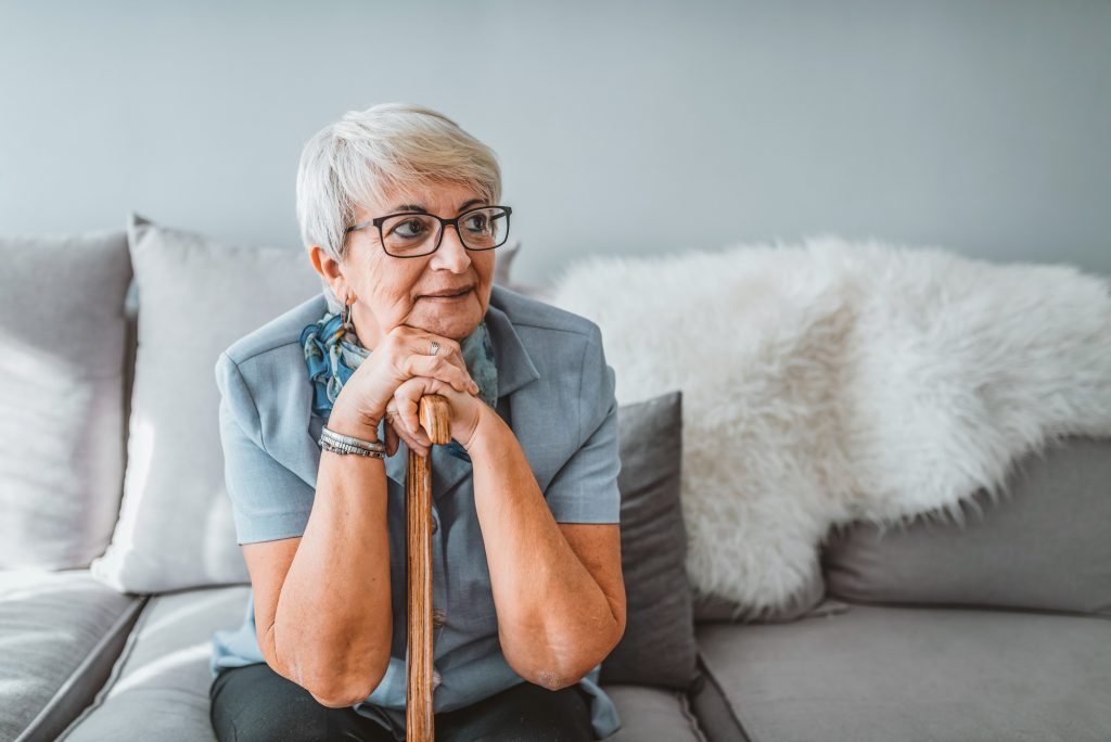 image of older woman with short grey hair, wearing glasses. She is sitting on a lounge leaning on a walking stick, looking off to the side.